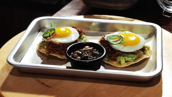Chicken Tinga Tostadas with Mango Guacamole and Wasabi infused sunny-side up egg